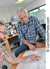 Man sat on table looking at plans with another man