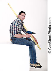 Man sat with power drill and length of wood
