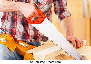 Man sawing. Close-up of handyman using saw in workshop