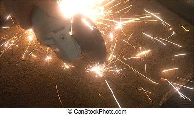 man sawing metal by grinder, working environment - man...
