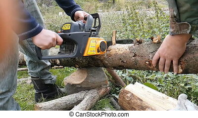 Man sawing wood slowmotion - Man sawing wood trunk with...