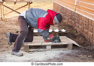 man saws a board with circular saw