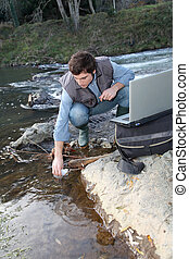 Man scientist testing quality of water in river