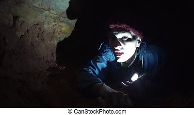 Man scrambles by ground inside cave illuminates way with...