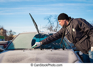 Man scraping front windshield