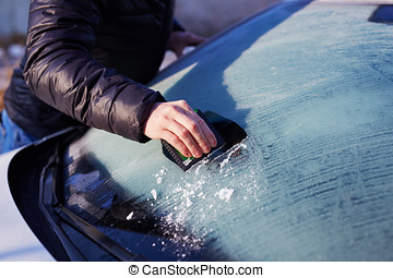 Man scraping ice from the windshield of a car