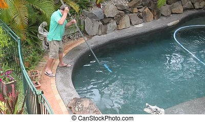 Man Scraping Pool - Middle aged man cleans his swimming pool...