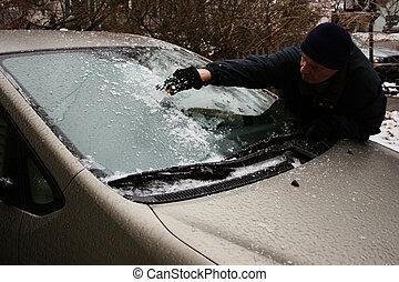 man scraping windshield