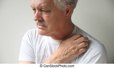 man scratches shoulder - an older man with a persistent itch...