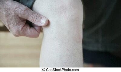 man scratching back of knee