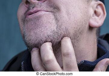 Man Scratching Beard - Matured sneering man scratching his...