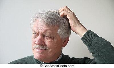 man scratching his head - senior man scratches his head...