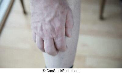 man scratching his leg