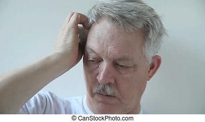 man scratching his scalp