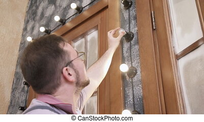 Man screws light bulbs into design lightning around door in house.