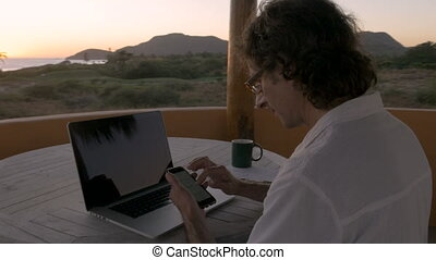 Man scrolling through smart phone at home office by ocean...