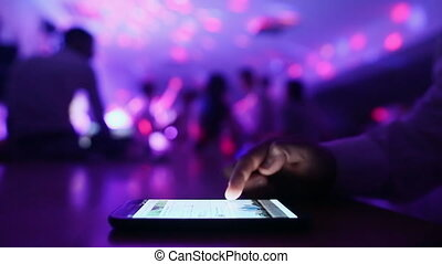 Man scrolls phone on the background the dancing people at a party.