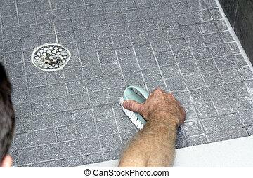 Man Scrubbing a Shower Floor