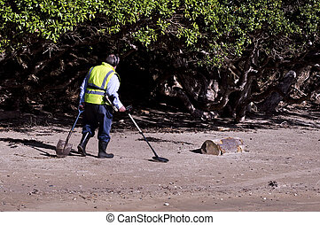 Man Search for Metals with Metal Detector