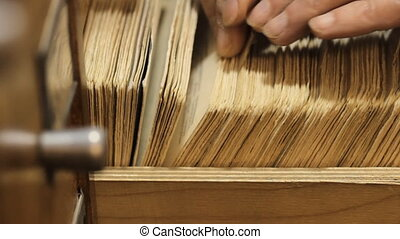 man searches something in card catalog