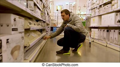 Man searching among shelves of appliance store - Side view...