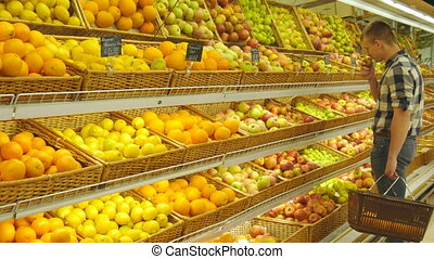 Man selecting fresh red apples in grocery store produce department and smelling it. Young handsome guy with shop basket is choosing apples in supermarket.