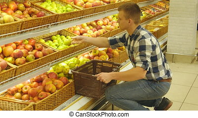 Man selecting fresh red apples in grocery store produce department and putting it in the basket. Handsome guy is choosing apples in supermarket and putting them into supermarket cart