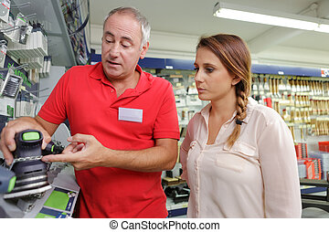 man seller consulting customer at cash desk in tool-ware...