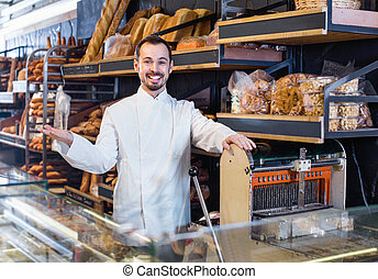Man seller displaying assortment of bakery