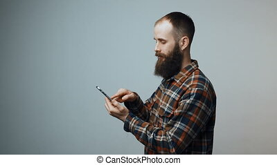 Man sending a sms on cell phone - Bearded man sending a sms...