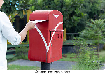 Man sending mail in the old mailbox in countryside.