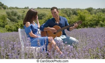 Man serenading his girlfriend with guitar in nature