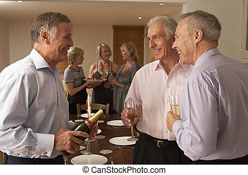 Man Serving Champagne To His Guests At A Dinner Party