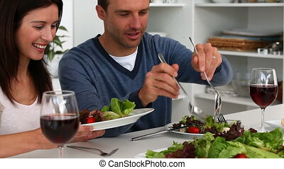 Man serving salad to his wife