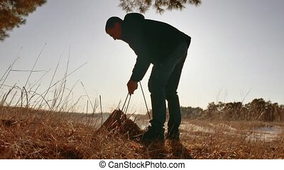 man sets bowler on burning campfire camping holiday in nature. a man tourist kindles is preparing bonfire a fire from the branches of trees sunlight. Boy Scout Kindle Campfire cooking food nature lifestyle Camping Outdoors Tourism Silhouette