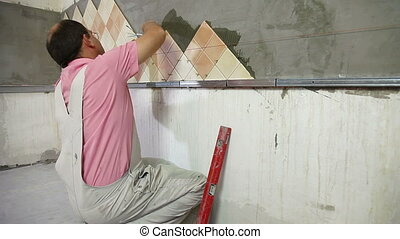 Man setting tile on cement board