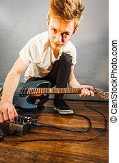 Man setting up guitar equipment