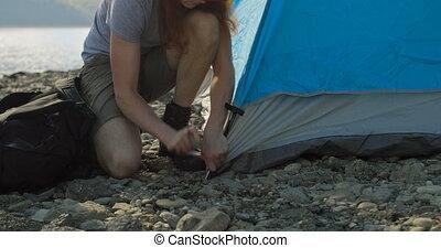 Man setting up tent near riverside 4k - Man setting up tent ...