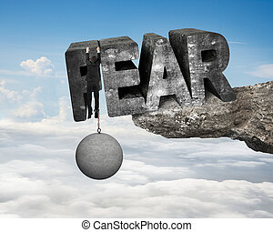Man shackled by heavy concrete ball hanging on big 3D fear mottled word at the edge of cliff with blue sky clouds background