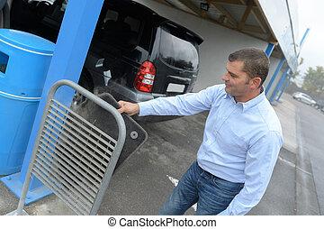 man shaking car mats