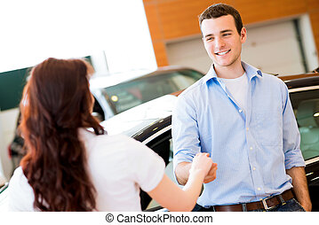 man shaking hands with car salesman