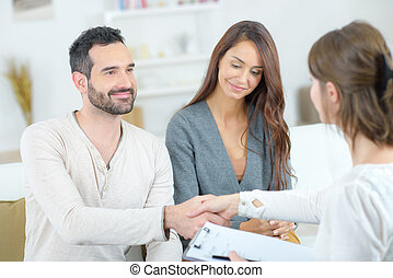 Man shaking hands with lady holding clipboard
