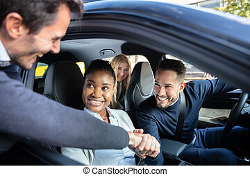 Man Shaking Hanks With Friends Sitting In Car