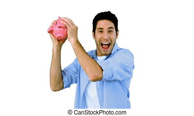 Man shaking piggy bank excitedly on white background in slow...