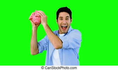 Man shaking piggy bank excitedly on green screen in slow...