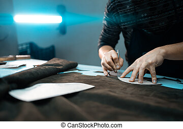 man shaping leather for shoe with knife on factory