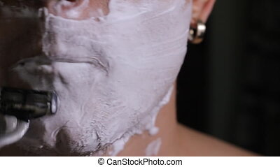 man shaves close up