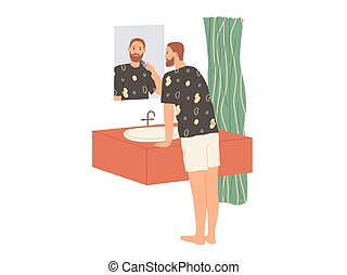 Man shaves his beard with an electric razor while standing in the bathtub by the mirror.