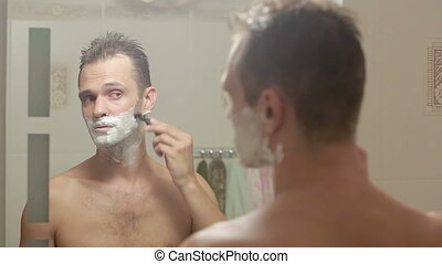 man shaves his face. handsome man shaving in the bathroom.