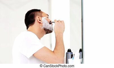 man shaving beard with safety razor at bathroom - beauty,...